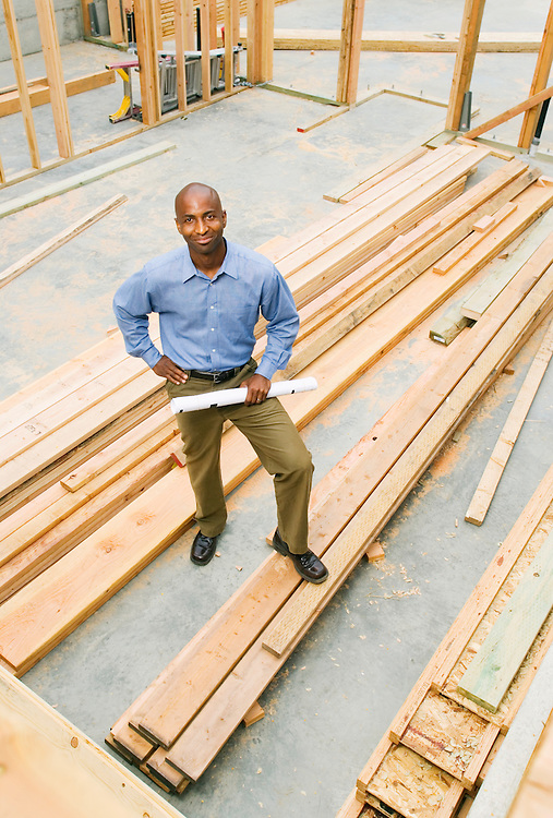 Portrait of an African American man standing in a construction site holding rolled up plans.