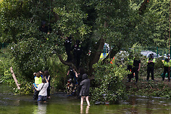 Denham, UK. 24 July, 2020. A large section of branch from an ancient alder tree cut by a tree surgeon working with the National Eviction Team falls into the river Colne close to environmental activists from HS2 Rebellion trying to protect the tree from destruction in connection with works for the HS2 high-speed rail link in Denham Country Park. 2020 is the Year of the Tree. The Metropolitan Police, Thames Valley Police, City of London Police and Hampshire Police were in attendance to enable HS2 to remove the tree.