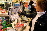 (MODEL RELEASED IMAGE). During the Le Moine family's weekly shopping trip to the huge Auchan hypermarket, Delphine prints a price tag for her tomatoes at a produce-weighing station. Hungry Planet: What the World Eats (p. 126). The Le Moine family lives in the Paris suburb of Montreuil, France, and is one of the thirty families featured, with a weeks' worth of food, in the book Hungry Planet: What the World Eats.