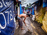 26 JANUARY 2018 - SANTO DOMINGO, ALBAY, PHILIPPINES: A man digs a drainage ditch for evacuees from the Mayon Volcano living in tents at Barangay Lidong shelter. The shelter is in school and all of the classrooms are already being used to house evacuees. Recent arrivals are living in tents on the school grounds. The volcano was relatively quiet Friday, but the number of evacuees swelled to nearly 80,000 as people left the side of  the volcano in search of safety. There are nearly 12,000 evacuees in Santo Domingo, one of the communities most impacted by the volcano. The number of evacuees is impacting the availability of shelter space. Many people in Santo Domingo, on the north side of the volcano, are sleeping in huts made from bamboo and plastic sheeting. The Philippines is now preparing to house the volcano evacuees for up to three months.      PHOTO BY JACK KURTZ