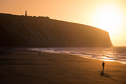 © Licensed to London News Pictures. 07/04/2016. Sandown, UK. People walking along the beach during sunrise at Yaverland on the Isle of Wight this morning, Thursday 7th April 2016. Photo credit : Rob Arnold/LNP