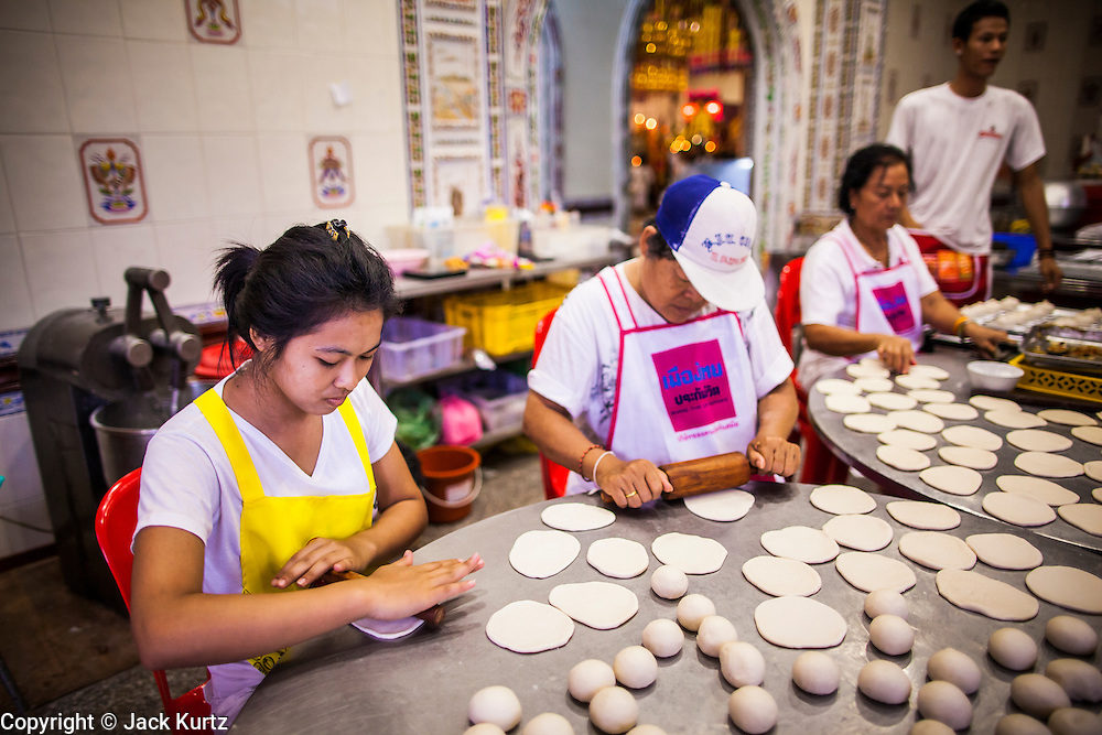 22 OCTOBER 2012 - HAT YAI, THAILAND: Women make vegetarian dumplings for the Vegetarian Festival at a Chinese temple in Hat Yai. The Vegetarian Festival is celebrated throughout Thailand. It is the Thai version of the The Nine Emperor Gods Festival, a nine-day Taoist celebration celebrated in the 9th lunar month of the Chinese calendar. For nine days, those who are participating in the festival dress all in white and abstain from eating meat, poultry, seafood, and dairy products. Vendors and proprietors of restaurants indicate that vegetarian food is for sale at their establishments by putting a yellow flag out with Thai characters for meatless written on it in red. Hat Yai was settled by Chinese traders centuries ago. The town still has a very large Chinese population. Hat Yai is the largest in southern Thailand. It is an important commercial center and tourist destination. It is especially popular with Malaysian, Singaporean and Chinese tourists.     PHOTO BY JACK KURTZ