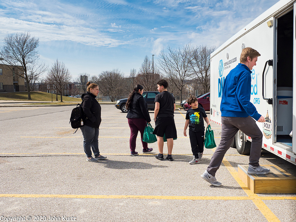 "17 MARCH 2020 - DES MOINES, IOWA: GRADY FOX, right, with the Boys & Girls Clubs and working with the Des Moines Area Religious Council (DMARC) walks back to the food distribution trailer in the parking lot of Carver Elementary School in Des Moines after giving bags of food to a family. Des Moines Public Schools are closed for at least 30 days because of the Coronavirus outbreak. Des Moines area religious organizations and food banks are working together to bring free food to children in at risk communities. Volunteers and workers are practicing ""social distancing"" by leaving the food packages on the pavement and recipients pick up the packages. Tuesday, the Governor of Iowa ordered all restaurants and bars to close or go to take out only. The Iowa Department of Public Health has urged all public buildings, like libraries and schools, to close, and all schools in Iowa are closed for at least 30 days.     PHOTO BY JACK KURTZ"