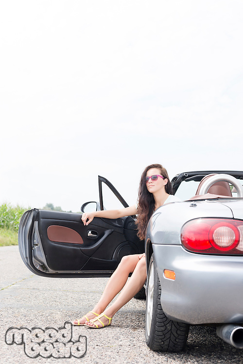 Young woman sitting in convertible on country road against clear sky