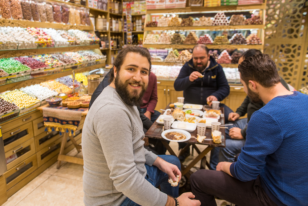 Young bearded turns and smiles while eating lunch with another group of men in shop at Istanbul Spice bazaar in Turkey