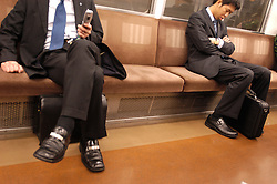 Two male commuters sitting in carriage on the Tokyo subway system in Japan