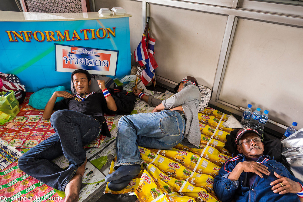 Anti-government protestors sleep at the Information counter in the Ministry of Finance complex in Bangkok. Protestors opposed to the government of Thai Prime Minister Yingluck Shinawatra spread out through Bangkok this week. Protestors have taken over the Ministry of Finance, Ministry of Sports and Tourism, Ministry of the Interior and other smaller ministries. The protestors are demanding the Prime Minister resign, the Prime Minister said she will not step down. This is the worst political turmoil in Thailand since 2010 when 90 civilians were killed in an army crackdown against Red Shirt protestors. The Pheu Thai party, supported by the Red Shirts, won the 2011 election and now govern. The protestors demanding the Prime Minister step down are related to the Yellow Shirt protestors that closed airports in Thailand in 2008.