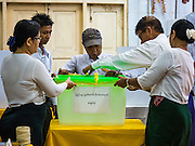 08 NOVEMBER 2015 - YANGON, MYANMAR:  Elections workers ensure that a ballot box is empty before voting started in Yangon Sunday. The citizens of Myanmar went to the polls Sunday to vote in the most democratic elections since 1990. The National League for Democracy, (NLD) the party of Aung San Suu Kyi is widely expected to get the most votes in the election, but it is not certain if they will get enough votes to secure an outright victory. The polls opened at 6AM. In Yangon, some voters started lining up at 4AM and lines were reported to long in many polling stations in Myanmar's largest city.     PHOTO BY JACK KURTZ