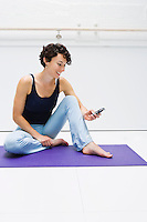 A young woman sitting on a yoga mat in a white room using her cell phone.