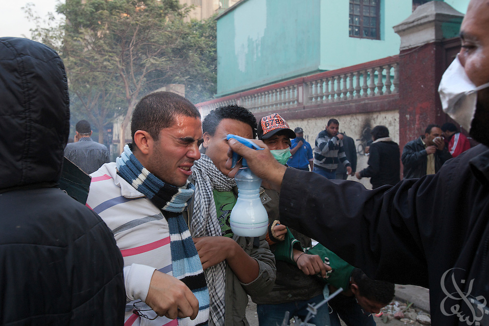 An Egyptian volunteer sprays vinegar solution to counter tear gas in the eyes of a wounded protestor during ongoing demonstrations November 20, 2011 near Tahrir square in central Cairo, Egypt.  Protestors demanding the transition of power from military to civilian control clashed with Egyptian security forces for a second straight day in central Cairo, with hundreds injured and at least 11 protestors killed.  (Photo by Scott Nelson)