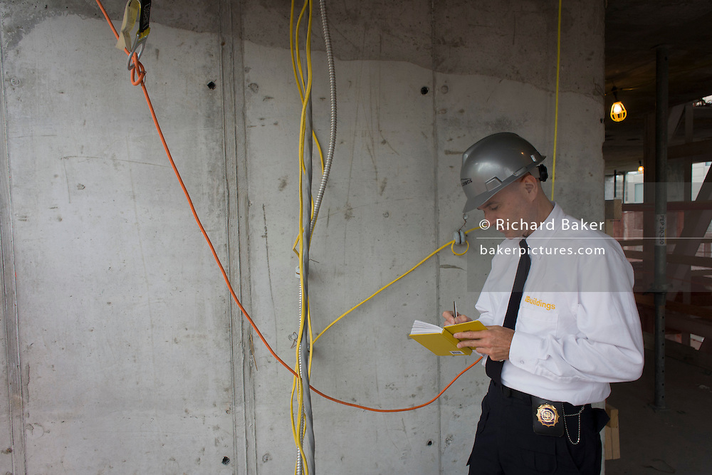 Investigative Engineering Services, Assistant Commissioner Tim Lynch inspects wiring on a new construction site in Manhattan, New York City.