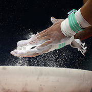 A gymnast chalks his hands before his Horizontal bar routine during the Senior Men Competition at The 2013 P&G Gymnastics Championships, USA Gymnastics' National Championships at the XL, Centre, Hartford, Connecticut, USA. 16th August 2013. Photo Tim Clayton