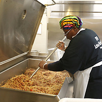 """Lauren Wood   Buy at photos.djournal.com<br /> Sherrell McWilliams mixes in seasoning, ground beef and tomato sauce after boiling spaghetti in a large tilt pan Friday morning at Lawndale Elementary School. McWilliams was preparing wheat noodle baked spaghetti to be served during lunch service at the school. """"A lot of people think we just heat things up, but we are making things from scratch,"""" said McWilliams"""