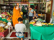 "11 AUGUST 2016 - BANGKOK, THAILAND: Buddhist monks lead a prayer with flower sellers in a florist's shop in Pak Khlong Talat in Bangkok. Pak Khlong Talat (literally ""the market at the mouth of the canal"") is the best known flower market in Thailand. It is the largest flower market in Bangkok. Most of the shop owners in the market sell wholesale to florist shops in Bangkok or to vendors who sell flower garlands, lotus buds and other floral supplies at the entrances to temples throughout Bangkok. There is also a fruit and produce market which specializes in fresh vegetables and fruit on the site. It is one of Bangkok's busiest markets and has become a popular tourist attraction.          PHOTO BY JACK KURTZ"