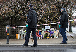 © Licensed to London News Pictures. 02/04/2018. London, UK. Members of a police search team pass tributes left near Ellerton Road in Wandsworth, south west London, where 20 year old Devoy Stapleton was stabbed to death at 1am on Sunday 1st April - the 31st fatal stabbing this year in the capital. It is being reported that London's murder rate has overtaken New York's.   Photo credit: Peter Macdiarmid/LNP