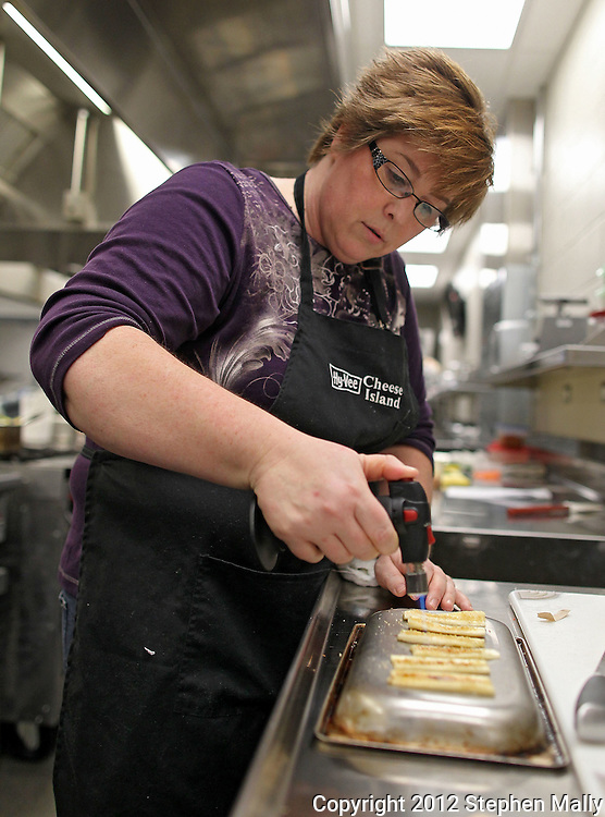 Maureen Lehman of Cedar Rapids uses a brulee torch to melt and brown the turbinado sugar on her banana slices during the Discovering International Foods: Japanese Cuisine class at The Hotel at Kirkwood Center in Cedar Rapids on Wednesday evening, February 15, 2012. (Stephen Mally/Freelance)