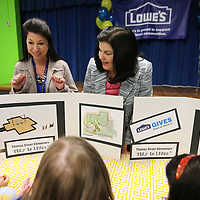 Michelle Guyton, Art teacher at Thomas Street Elementary School, and Cindy Pike, Thomas Street Elementary School Principal, look over the playground plans with a group of kindergartners after the announcement of a $34,408.00 grant from the Lowe's Gives Foundation. Guyton wrote the grant for the play to learn project that will place two new playgrounds at the school that will transform an unused area into an inviting learning enviroment for all students.