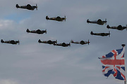 A formation of 12 spitfires forms up, flies past and lands - Duxford Battle of Britain Air Show taking place during IWM (Imperial War Museum) Duxford's centenary year. Duxford's principle role as a Second World War fighter station is celebrated at the Battle of Britain Air Show by more than 40 historic aircraft taking to the skies.