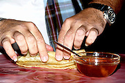 rolling a honey filled Mofletta, a traditional North African-Jewish sweet pastry that is usually eaten during the Mimouna celebration on the day after Passover. served with a sweat spread filling such as Honey or Chocolate.