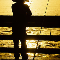 Picture of Balboa Pier Fisherman Fishing in Newport Beach California. Balboa Pier is located on Balboa Peninsula and is a popular spot in Orange County for fishing in the Pacific Ocean.