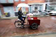 In Utrecht rijdt een vrouw met een kindje in de bakfiets door de stromende regen. <br /> <br /> In Utrecht a woman cycles with a child in a cargo bike in the pouring rain.