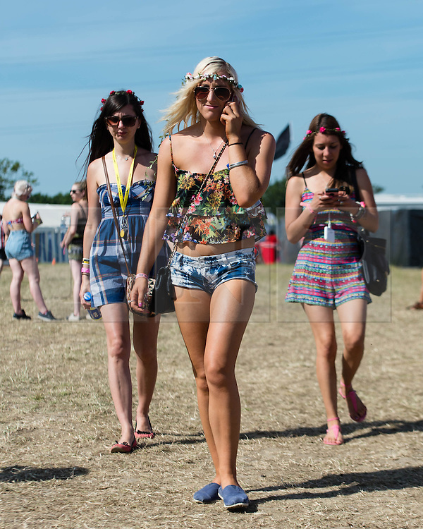 © Licensed to London News Pictures. 13/06/2014. Isle of Wight, UK.   Girls in festival dress walk in the early morning sun at Isle of Wight Festival 2014 - today is expected to be the hottest day of the year in the UK.   The Isle of Wight festival is an annual music festival that takes place on the Isle of Wight. Photo credit : Richard Isaac/LNP
