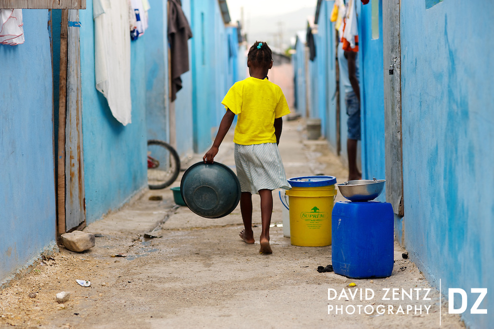 A girl holding a bowl walks down an alley between colorful homes in La Saline, Port au Prince, Haiti, on May 13, 2012. The houses were built by charity organizations following the devastating 7.0 earthquake of 2010.