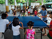 20 JANUARY 2018 - CAMALIG, ALBAY, PHILIPPINES: Children play ping pong at the Barangay Cabangan evacuee shelter in a school in Camalig. There are about 650 people living at the shelter. They won't be allowed to move back to their homes until officials determine that Mayon volcano is safe and not likely to erupt. More than 30,000 people have been evacuated from communities on the near the Mayon volcano in Albay province in the Philippines. Most of the evacuees are staying at school in communities outside of the evacuation zone.  PHOTO BY JACK KURTZ