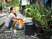 04 FEBRUARY 2015 - BANGKOK, THAILAND:  A woman does her family's dishes along railroad tracks in a working class neighborhood of Bangkok. After months of relative calm following the May 2014 coup, tensions are increasing in Bangkok. The military backed junta has threatened to crack down on anyone who opposes the government. Relations with the United States have deteriorated after Daniel Russel, the US Assistant Secretary of State for Asian and Pacific Affairs, said that normalization of relations between Thailand and the US would depend on the restoration of a credible democratically elected government in Thailand.   PHOTO BY JACK KURTZ