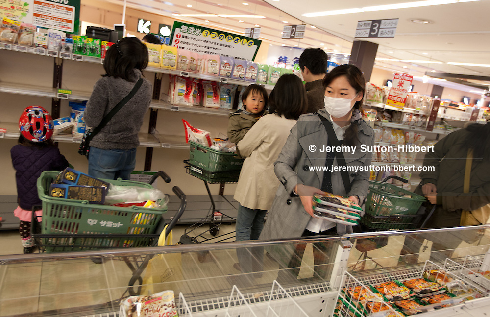 Shoppers in the rice aisle of the supermarket stock up from the already bare, but normally well stocked, shelves of rice and frozen rice. Supermarket shelves begin to empty as people become aware of the post-earthquake reality. People begin panic buying and emptying shelves of noodles, bottled water, rice, eggs, and other foods, in Mitakadai district of Tokyo, Japan, on Sunday 13th March 2011.