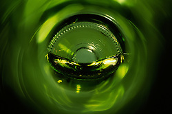"""Beauty at the Bottom: White Wine 3""- This image is a photograph of a wine bottle shot right down the mouth of the bottle. A television provides the main light source"