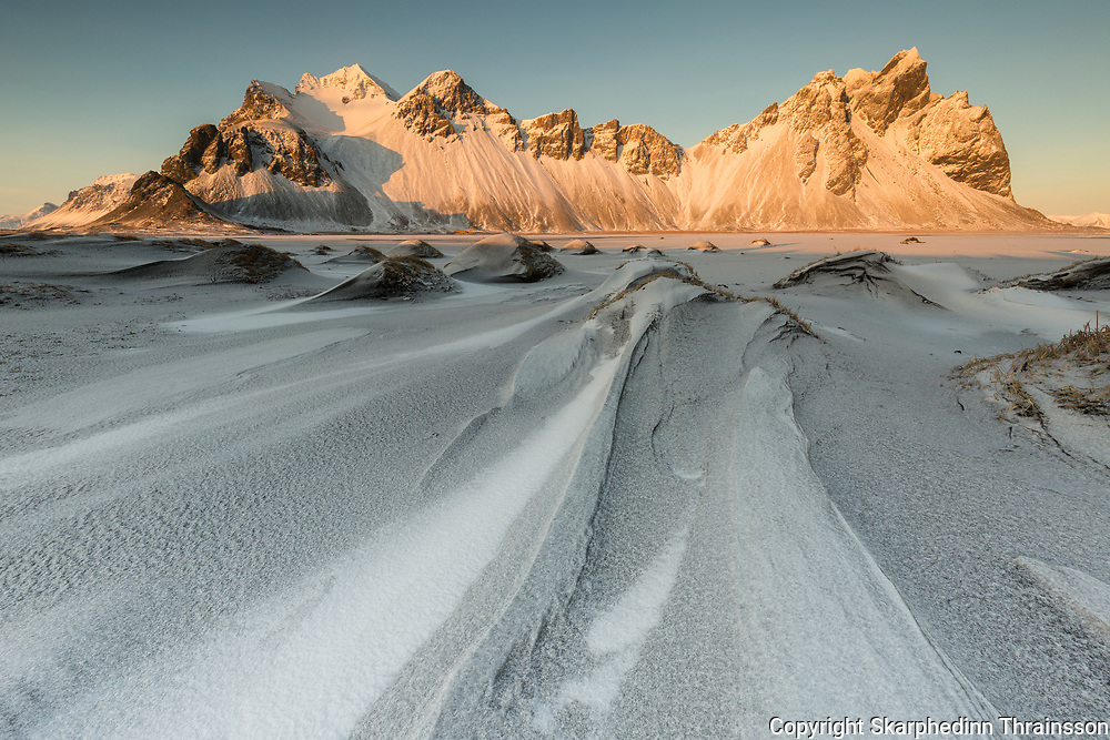 February 11 – Mt. Vestrahorn located in Stokksnes during the golden hour just after fresh snowfall on top of the black sands in front.<br /> <br /> <br /> Vestrahorn, Stokksnes