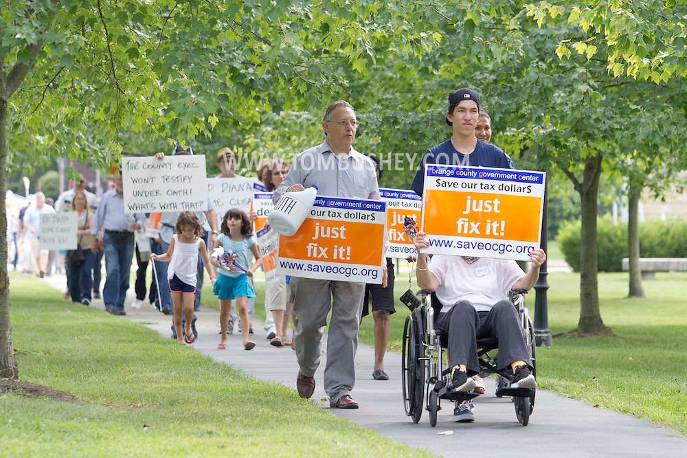Goshen, New York -    People march with  signs past the Orange County Government Center to show their support for restoring the building and for saving Valley View, the county-owned nursing home. The building was closed by Orange County Executive Ed Diana after water damage from Tropical Storm Irene, and the county is debating whether to replace or repair the structure. The building was designed in the brutalist style by noted architect and dean of the Yale School of Architecture Paul Rudolph in 1963 and built in 1967.