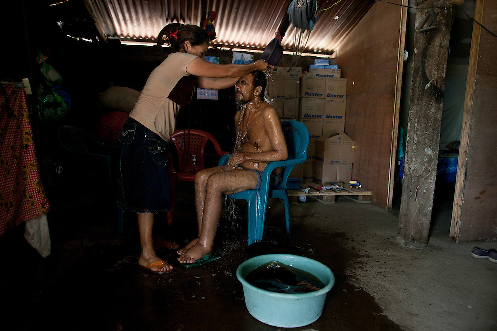 In this photo taken Wednesday, Jan. 18, 2012, Emma Vanegas, bathe of her husband Segundo Zapata, 49, chronic renal failure patient and former sugar cane cutter of the San Antonio sugarmill, inside a his house in Chichigalpa, Nicaragua. Zapata work during 20 years in the San Antonio sugarmill. A mysterious epidemic is devastating the Pacific coast of Central America, killing more than 24,000 people in El Salvador and Nicaragua since 2000 and striking thousands of others with chronic kidney disease at rates unseen virtually anywhere else. Many of the victims were manual laborers or worked in the sugarcane fields that cover much of the coastal lowlands.