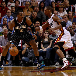 March 3, 2011; Miami, FL, USA; Orlando Magic center Dwight Howard (12) is guarded by Miami Heat power forward Chris Bosh (1) during a game at the American Airlines Arena. The Magic defeated the Heat 99-96.    Mandatory Credit: Derick E. Hingle