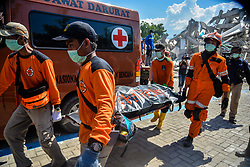 Oct. 1, 2018 - Palu, Sulawesi, Indonesia - Emergency rescue members transfer a body at a collapsed hotel in Palu, Central Sulawesi. Over 1,203 people were killed in Palu, Donggala district, Parigi Mountong district and North Mamuju district, after the 7.7 magnitude earthquake and the following tsunami. (Credit Image: © Iqbal Lubis/Xinhua via ZUMA Wire)