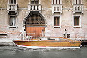 Wooden boat and palazzo on the Grand Canal, Venice, Veneto, Italy