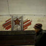KIEV, UKRAINE - February 25, 2014: A woman passes by a soviet era mural in Arsenalia Metro station, Kiev. CREDIT: Paulo Nunes dos Santos