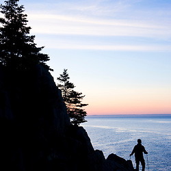 A lone hiker at sunrise on the Bold Coast trail in Cutler, Maine. Cutler Coast Public Reserved Land.