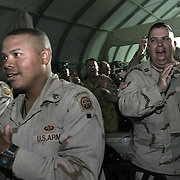 Soldiers react to the appearance of Pres. Bush as he spends Thanksgiving dinner with troops of the 1st Armor Division in a mess hall at Baghdad International Airport Thursday, November 27, 2003.  In a clandestine night time move President Bush, with the knowledge of only a handful of senior staff, departed his ranch in Crawford, Texas and flew through the night to spend the Thanksgiving Day holiday visiting troops stationed in the war torn country...Photo by Khue Bui