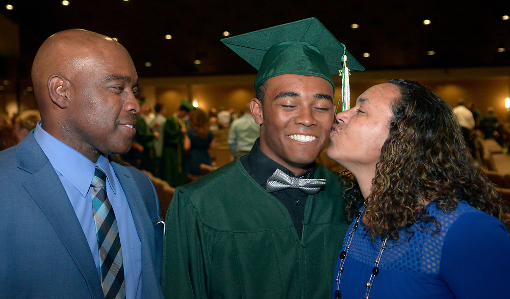 gbs051817f/ASEC -- DeShawn Lee gets a kiss from his mother, Shannon, as his dad David looks on, after Hope Christian High School graduation ceremonies at Calvary Albuquerque Church on Thursday, May 18, 2017. (Greg Sorber/Albuquerque Journal)