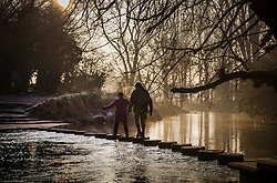 © Licensed to London News Pictures. 22/01/2017. Dorking, UK.  A couple cross the stepping stones over the River Mole near Dorking after another night of below freezing temperatures.  Photo credit: Peter Macdiarmid/LNP