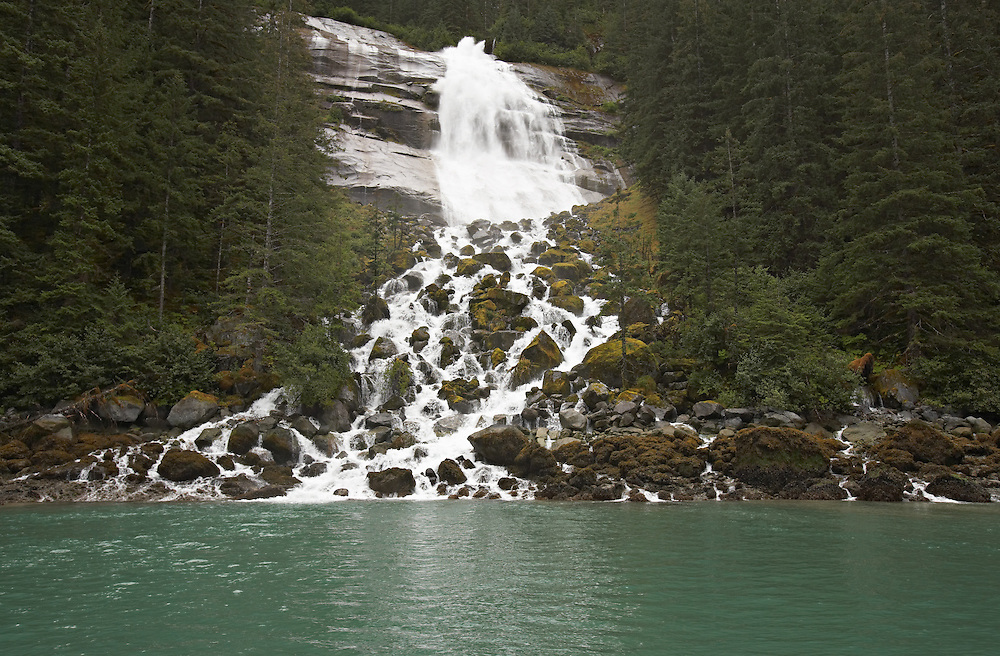 Waterfall in the Tongass National Forest carrying fresh water to the salt water of a fjord of Tracy Arm - Fords Terror Wilderness.  Southeast.  Inside Passage.  Summer.  Afternoon.