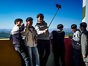 PAJU, GYEONGGI, SOUTH KOREA: South Korean tourists take selfies with a smart phone at Dora Observatory, on the edge of the DMZ. North Korea will be in the background of their selfie. Tourism to the Korean DeMilitarized Zone (DMZ) has increased as the pace of talks between South Korea, North Korea and the United States has increased. Some tours are sold out days in advance.      PHOTO BY JACK KURTZ