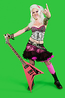 Portrait of young punk woman holding guitar with rock & roll hand sign over green background