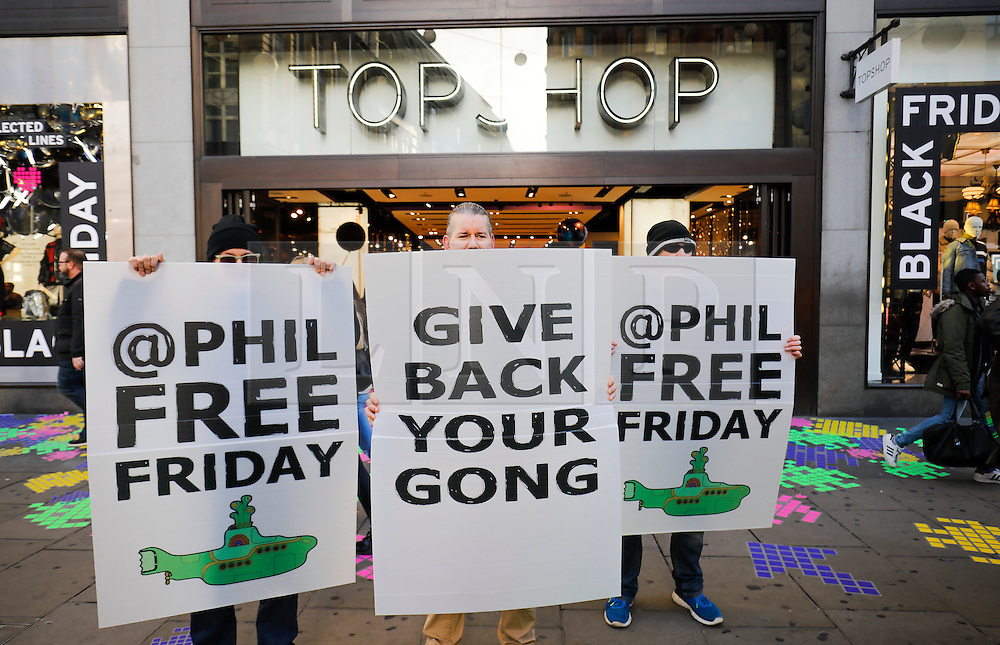 """© Licensed to London News Pictures. 25/11/2016. London, UK. An anti Philip Green demonstration outside TOPSHOP on Oxford Street, London, in the early hours on """"Black Friday"""". Sales from this years Black Friday event are expected to top £2 billion. Photo credit: Tolga Akmen/LNP"""