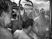 Swimmers shower and wash with disinfectant after completing the 2003 Liffey Swim. Dublin Ireland.