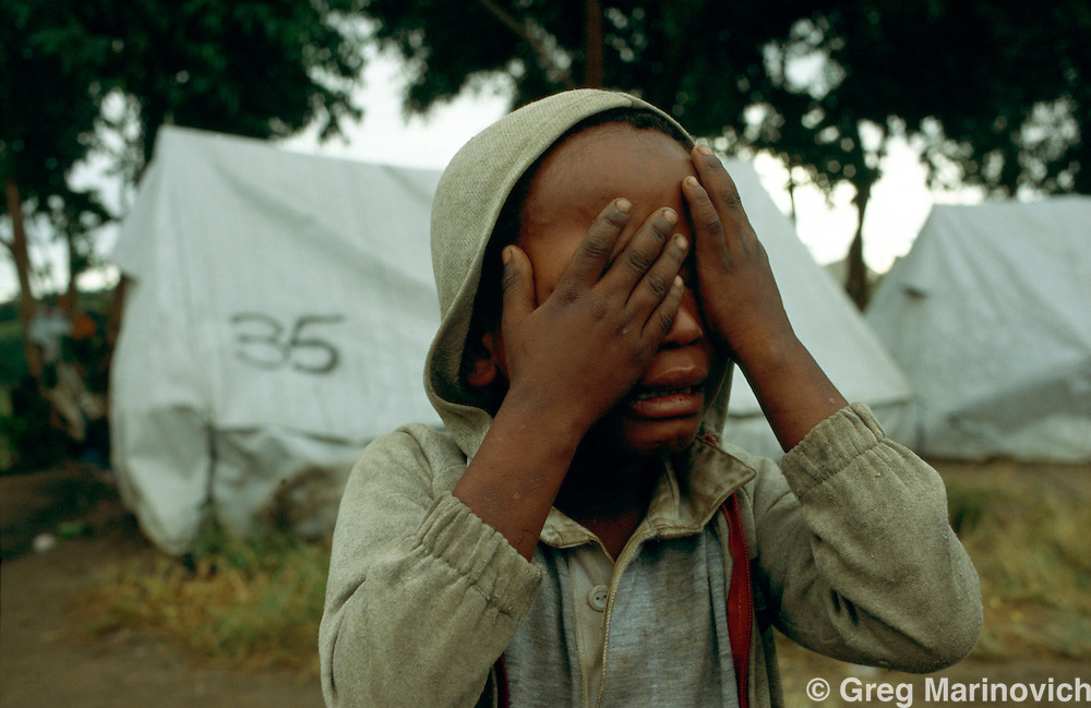 Sonkombo, KwaZulu Natal, 1994, South Africa: A young boy covers his eyes in a game at a refugee camp for ANC supporting families from the Sonkombo area from which they had fled months earlier because of attacks by rival IFP.