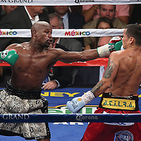 LAS VEGAS, NV - SEPTEMBER 13: (L-R) Floyd Mayweather Jr. v Marcos Maidana during their WBC/WBA welterweight title fight at the MGM Grand Garden Arena on September 13, 2014 in Las Vegas, Nevada. (Photo by Alex Menendez/Getty Images) *** Local Caption *** Floyd Mayweather Jr; Marcos Maidana