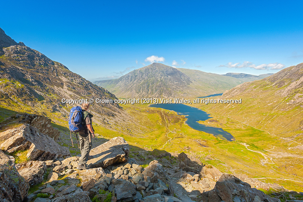 Walker on path down from devils Kitchen to Cwm Idwal with Llyn Idwal and Pen yr Ole Wen in shot<br /> Ogwen Valley<br /> Snowdonia<br /> Gwynedd<br /> North<br /> Walking<br /> Activitirs and Sports